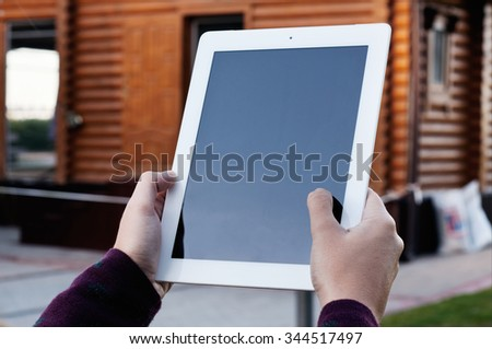 White tablet computer in the hands of the girl against the backdrop of a wooden house closeup. Copy space - stock photo