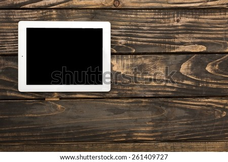 White tablet computer with isolated screen on an old wooden desk - stock photo