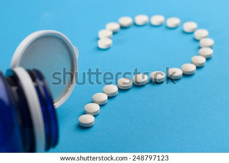 White Tablets On Blue Background As Question Mark - stock photo