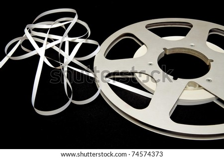 white tape unwound from a large spool of silver on a black background - stock photo