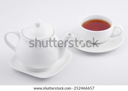 white tea cup with black tea and white teapot on white background - stock photo
