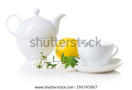 White teacup, teapot with herbal tea  - stock photo