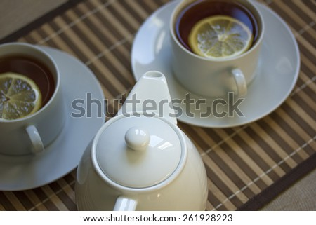 White teapot and two teacups with tea and lemon on straw plate. Shallow DOF - stock photo