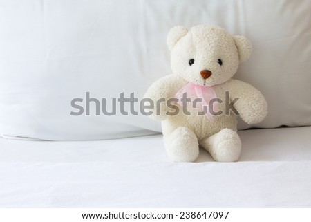 White  teddy bear alone on white bed - stock photo