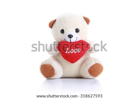 White teddy bear doll holding heart shaped pillow with love, isolated on white background - stock photo
