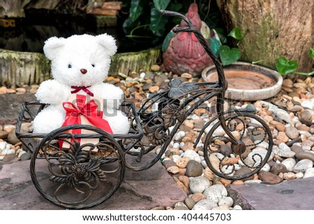 white teddy bear holding present on bicycle in garden background, love concept for valentines day - stock photo
