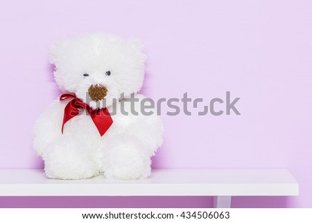 White teddy bear on shelf. White doll bear on the pink background. - stock photo