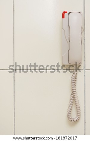 white telephone on gray wall - stock photo
