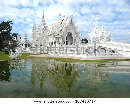White temple (Wat RongKhun) and reflection over cloudy sky. - stock photo