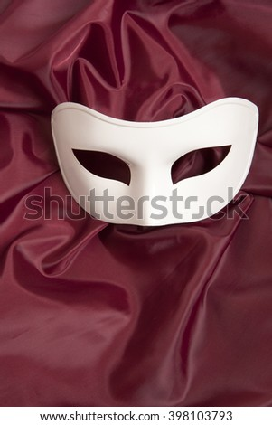 White theatrical mask and red silk fabric  - stock photo