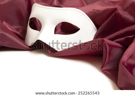 White theatrical mask and red silk fabric on a white background  - stock photo