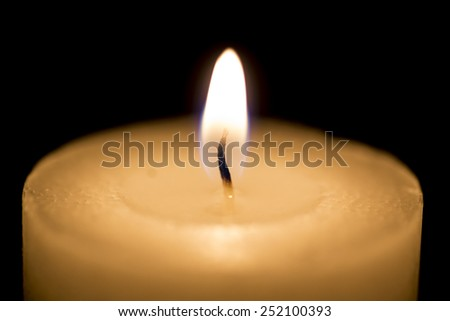 White thick candle with small flame on black - stock photo