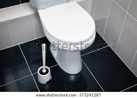 white toilet, black tiles on the floor - stock photo