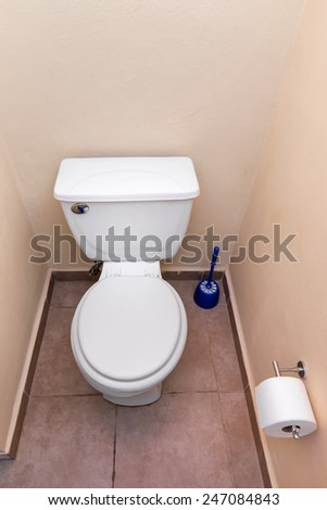 White toilet bowl and toilet paper in a bathroom interior - stock photo