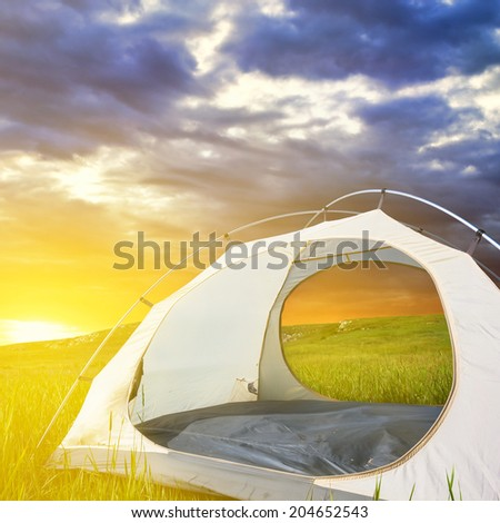 white touristic tent among a field at the sunrise - stock photo