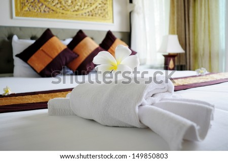 White towel in crab shape and a frangipani flower on white bed in relaxation bedroom of luxury boutique hotel - stock photo