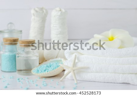White towel with Plumeria flower soap and aromatherapy spa tools, coconuts oil, blue aroma spa salt, herbal compress balls, seashells, starfish on white wooden background - stock photo