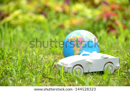 White toy car with terrestrial earth, environmental protection concept - stock photo