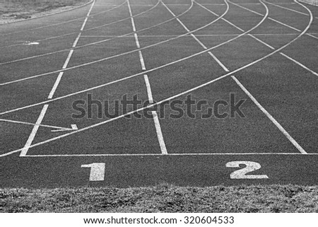 White track number on red rubber racetrack, texture of running racetracks in small stadium. Black and white photo - stock photo