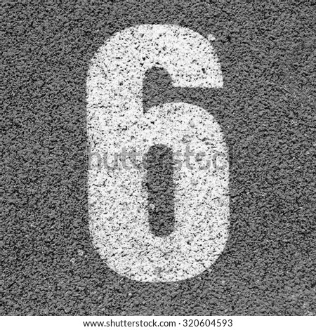 White track number on rubber racetrack, texture of running racetracks in small stadium. Black and white photo - stock photo