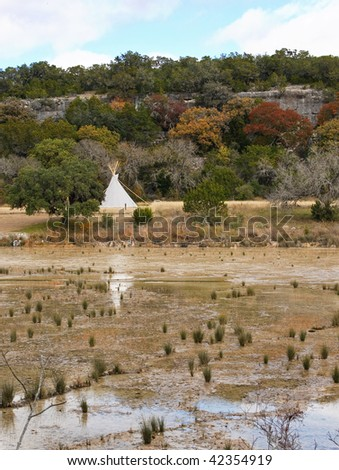 White traditional native american dwelling on the banks of a shallow river - stock photo