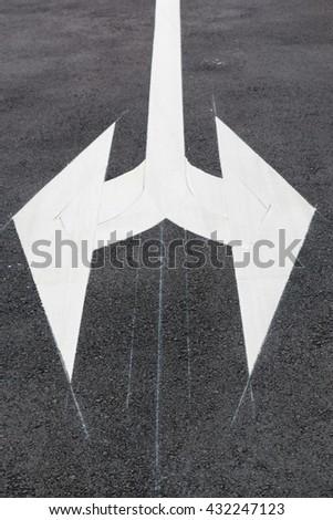 White traffic arrow signage on an asphalt road - stock photo