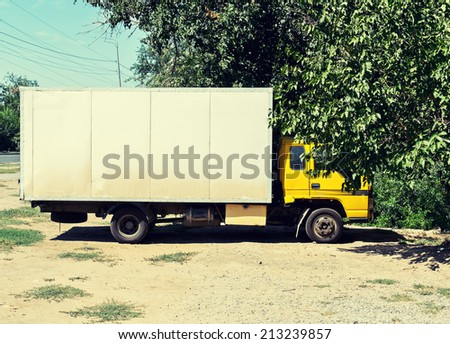 White truch parked near tree side view. - stock photo