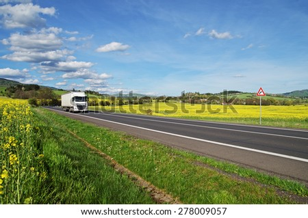 White truck driving on the asphalt road between yellow flowering rapeseed field in the rural landscape. Wooded mountains in the background. Blue sky with white clouds. - stock photo