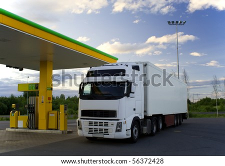 White truck is at a fuel station. - stock photo