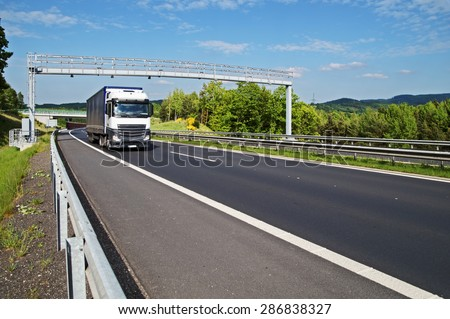 White truck passing through the electronic toll gates on the highway in a wooded landscape. Bridge and forested mountains in the background. White clouds in the blue sky. - stock photo