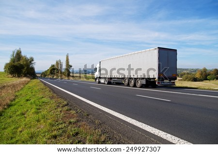 White truck travels on the asphalt road in the countryside. Fields, meadows and trees in early autumn colors in the background. - stock photo