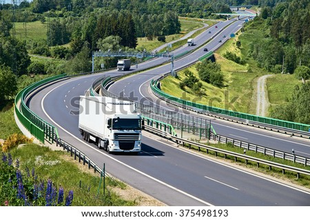 White trucks traveling on the asphalt highway with electronic toll gates in a wooded landscape. View from above. Sunny summer day. - stock photo