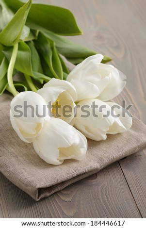 white tulips on old wood table, spring flowers - stock photo