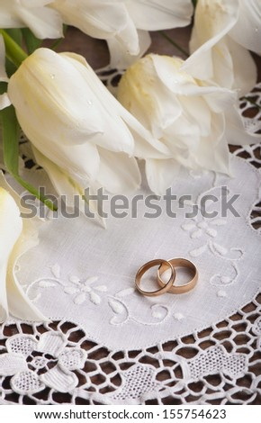 white tulips on old wooden boards  and couple of wedding rings - stock photo