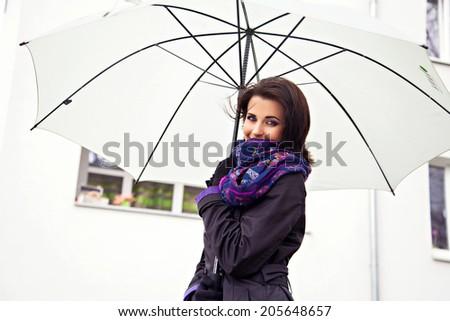 White umbrella in hands of beautiful woman - stock photo