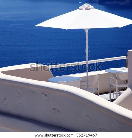 White umbrella on greek balcony resort house and Aegean sea in Oia, Santorini island, Greece. Square toned image - stock photo