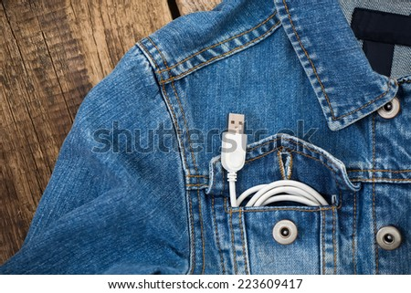 white USB cable in jeans pocket, USB cord with the jeans pocket on wooden background - stock photo