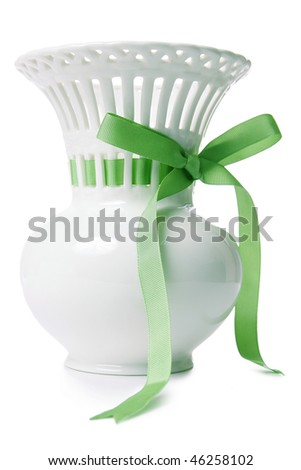 White vase with green bow over white background - stock photo