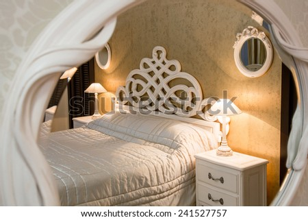White vintage style carved bed and nightstand with lamps sen through the carved mirror - stock photo