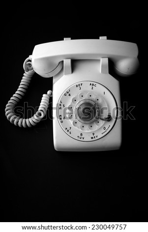 White vintage telephone with rotary dial isolated on black - stock photo