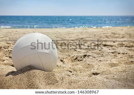 White volleyball sits on top of the sand.  - stock photo