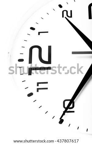 White wall clock with black arrows. Selective focus. Shallow depth of field. Toned. - stock photo