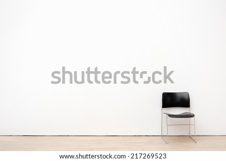 White wall texture with a chair - stock photo