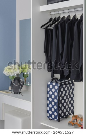 white wardrobe with row of black shirts and dressing table at home - stock photo