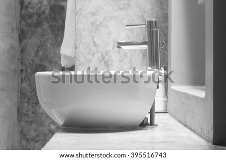 white wash basin on cement countertop. - stock photo