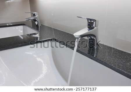 white washbasins and faucet on granite counter with water drop - stock photo