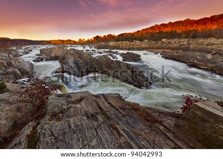 White water river with silky flow in warm sunset light - stock photo