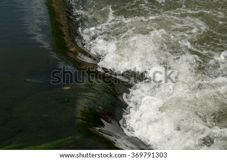 White water splashing and fothing as it passes over the weir at County Lock on the Kennet and Avon Canal in the centre of Reading, Berkshire. - stock photo