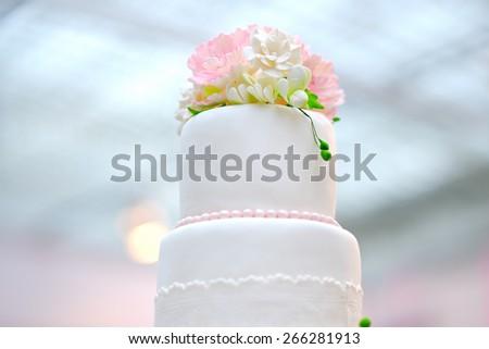 White wedding cake decorated with cream flowers  - stock photo