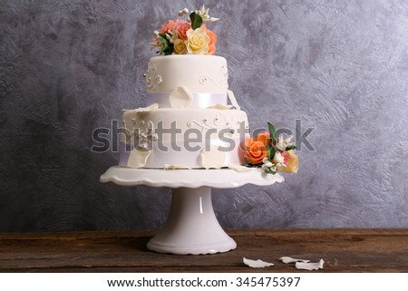White wedding cake decorated with flowers on wooden table against grey background - stock photo
